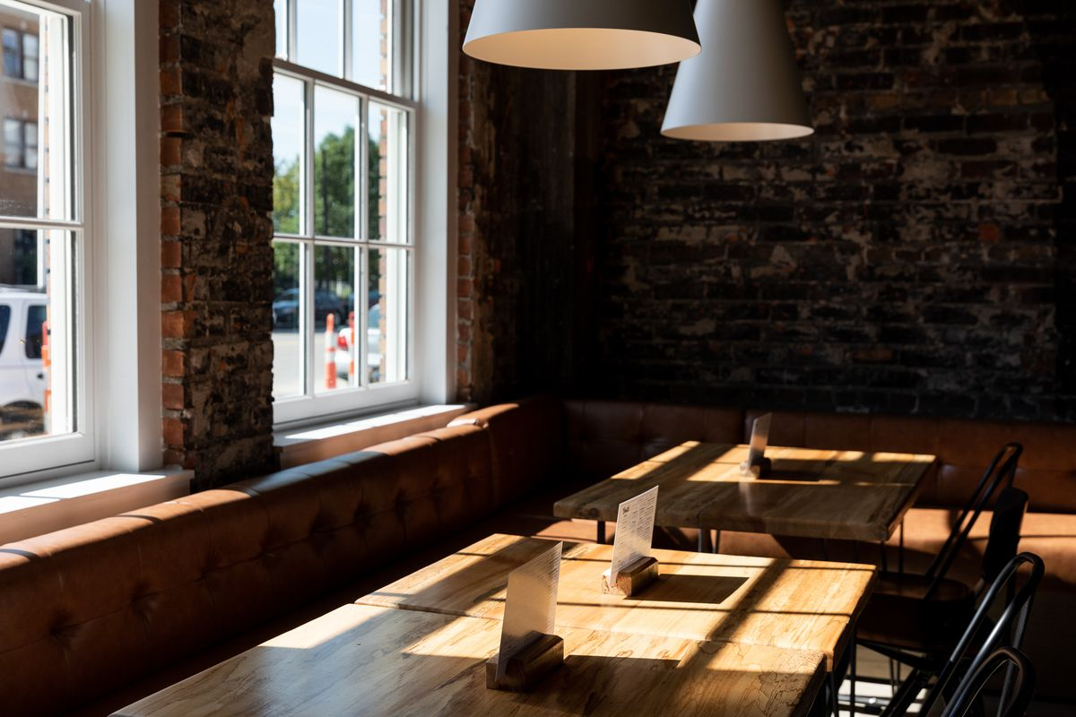 Sun streams over tables with leather banquette seats.