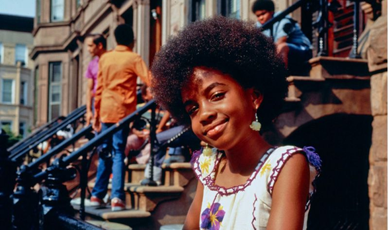 A girl smiles knowingly at a camera while people stand on a stoop behind her.