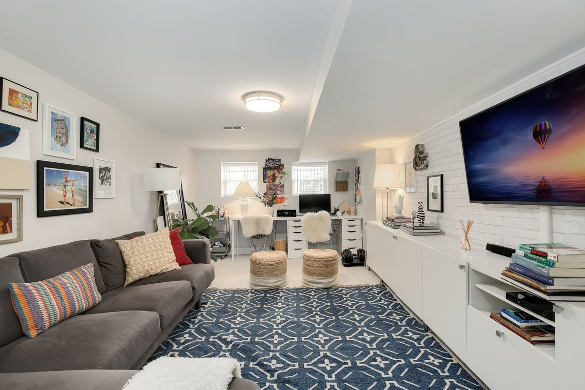 Two desks sit at the end of the room under small windows. A couch faces a tv and a long wall-length cabinet. Framed photos, stacked art books, and colorful pillows liven up the lower level.