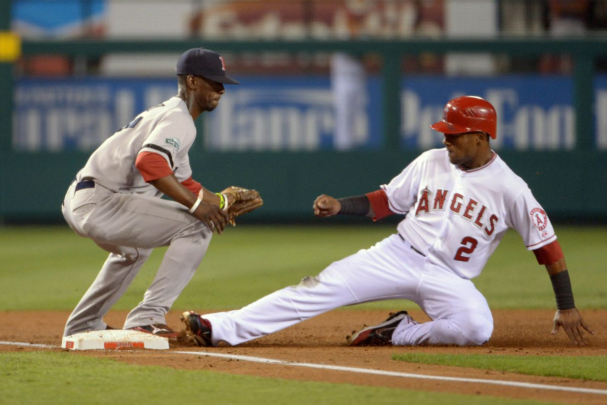 Erick Aybar (2) slides into third base to beat a throw to Boston Red Sox third baseman Pedro Ciriaco (77) in the second inning at Angel Stadium. Mandatory Credit: Kirby Lee/Image of Sport-US PRESSWIRE