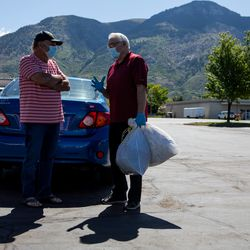 """Mike Nivens, left, speaks with Grant Protzman, right, while he holds bags of Nivens' donations to a collection for the Ogden Rescue Mission and the Lantern House outside Kirt's Family Drive Inn in Ogden on Monday, May 25, 2020. """"I've been surprised, many people said 'thanks for giving us the opportunity to help, we just didn't know how,'"""" Protzman said. """"There's a real need."""""""