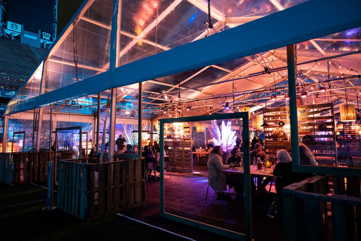 An outdoor dining tent that shows tables filled with customers at Seattle's Lumen Field