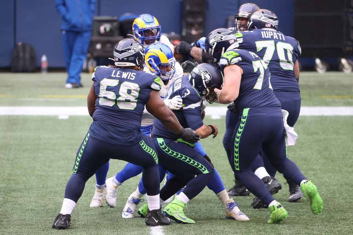 Quarterback Russell Wilson #3 of the Seattle Seahawks is sacked by defensive end Aaron Donald #99 of the Los Angeles Rams during the first quarter of the NFC Wild Card Playoff game at Lumen Field on January 09, 2021 in Seattle, Washington.