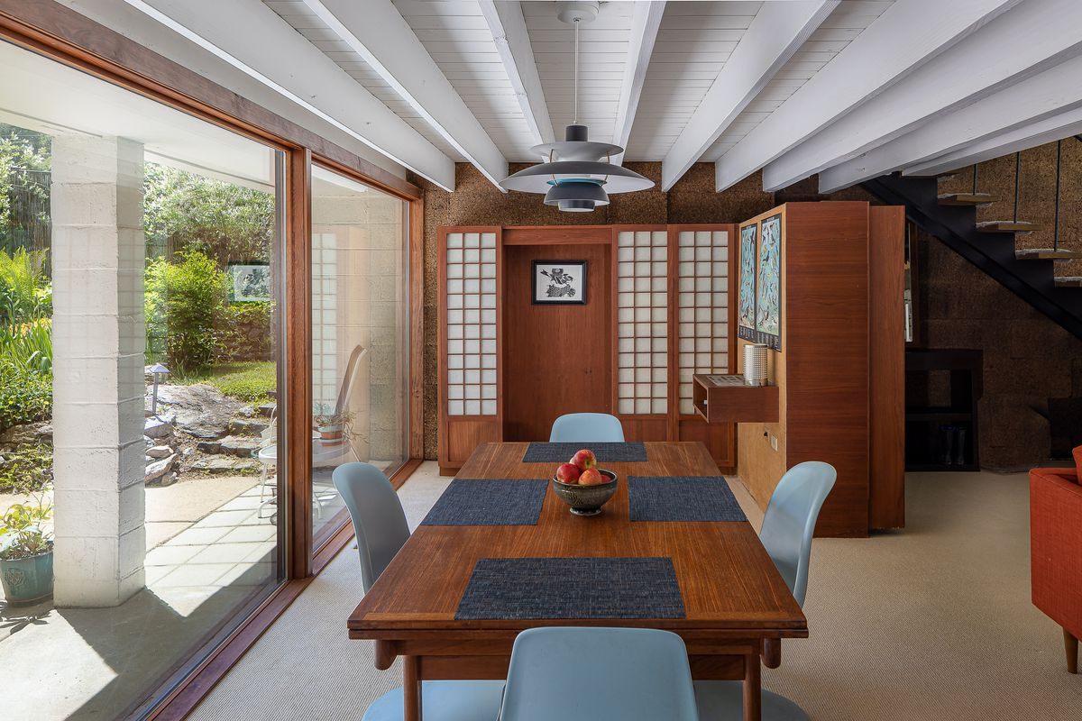 A dining room with a wooden table, four blue chairs, and a Japanese room divider in the background.