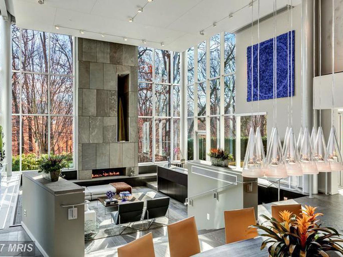 The interior of a house in Washington D.C. There are chairs, tables, desks, floor to ceiling windows, and a fireplace.
