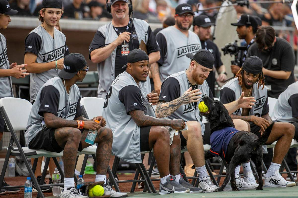 Las Vegas Raiders Josh Jacobs (28, center) looks on as teammate Max Crosby (98) and Damon Arnette (20) play with bat dog Finn during a charity softball game versus the Vegas Golden Knights at the Las Vegas Ballpark on Saturday, July 24, 2021 (L.E. Baskow/Las Vegas Review-Journal) @Left_Eye_Images