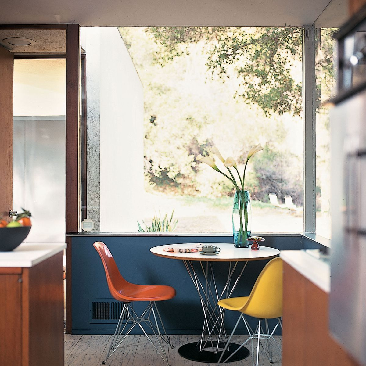 A circular table and two colorful chairs adjacent to two large window panes.