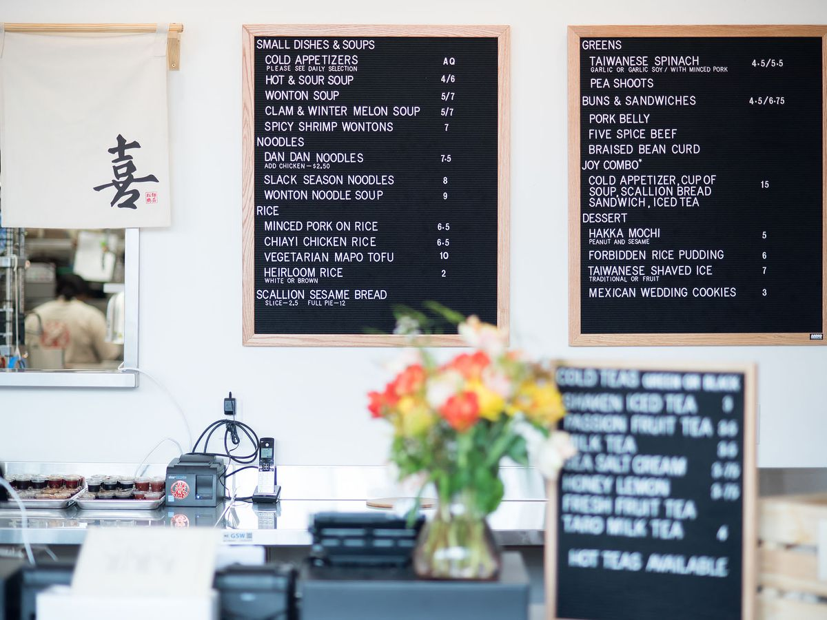 Joy, a modern Taiwanese restaurant, shows off its menu with some flowers around.