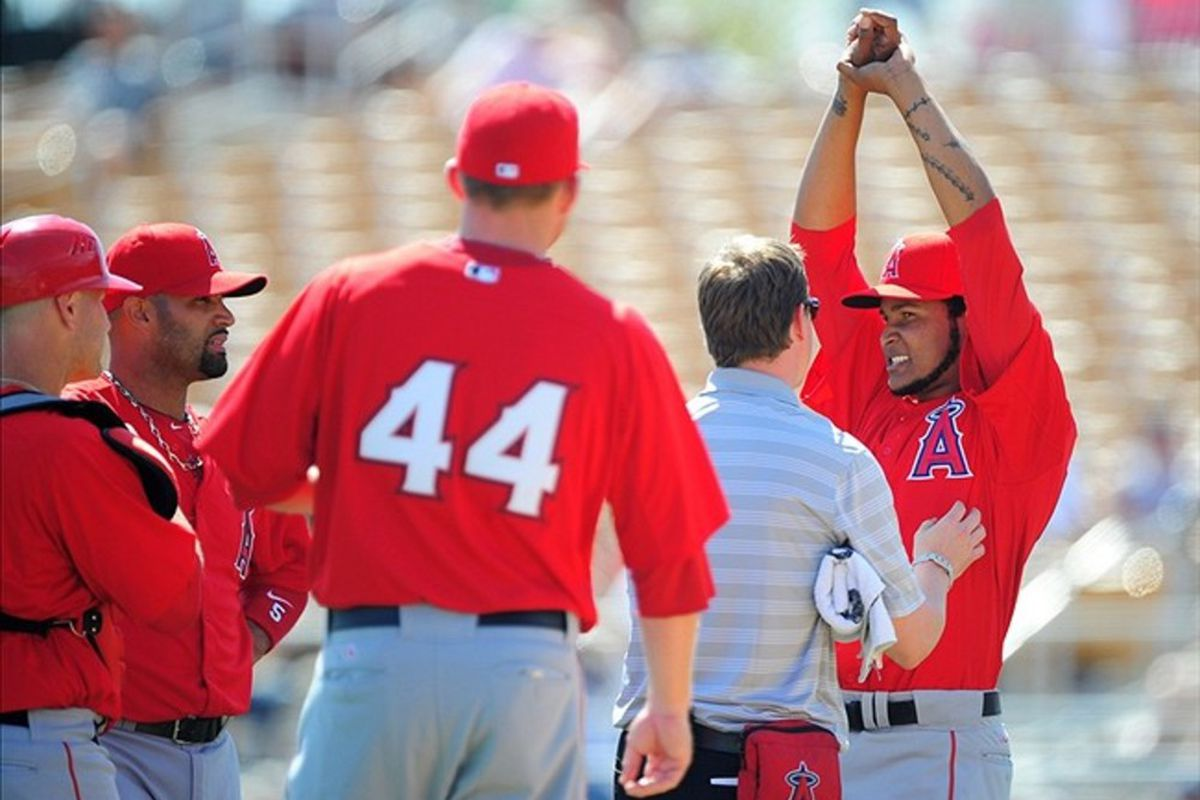 Ervin Santana <em>(right)</em> reacts as he is tended to by a trainer after being hit by a line drive in the second inning.