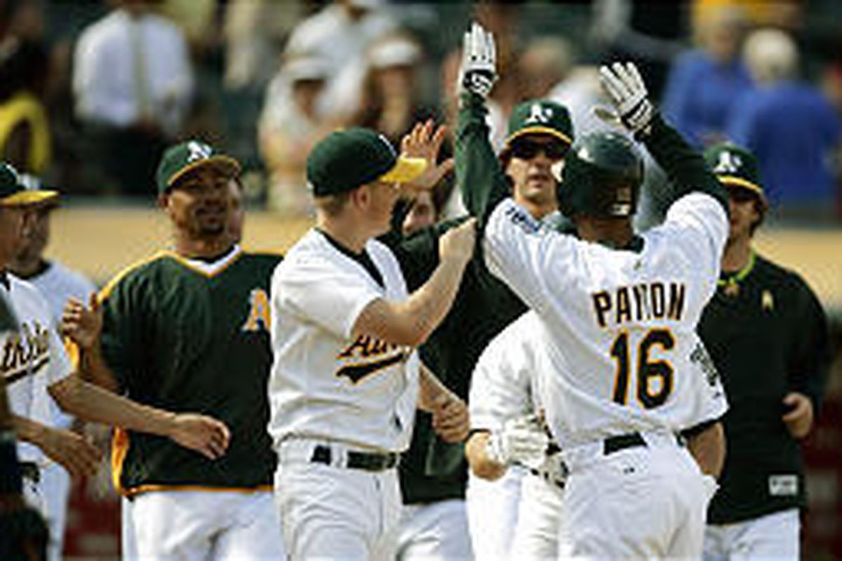 The Oakland Athletics mob Jay Payton (16) as he scores the winning run in the ninth vs. Seattle.