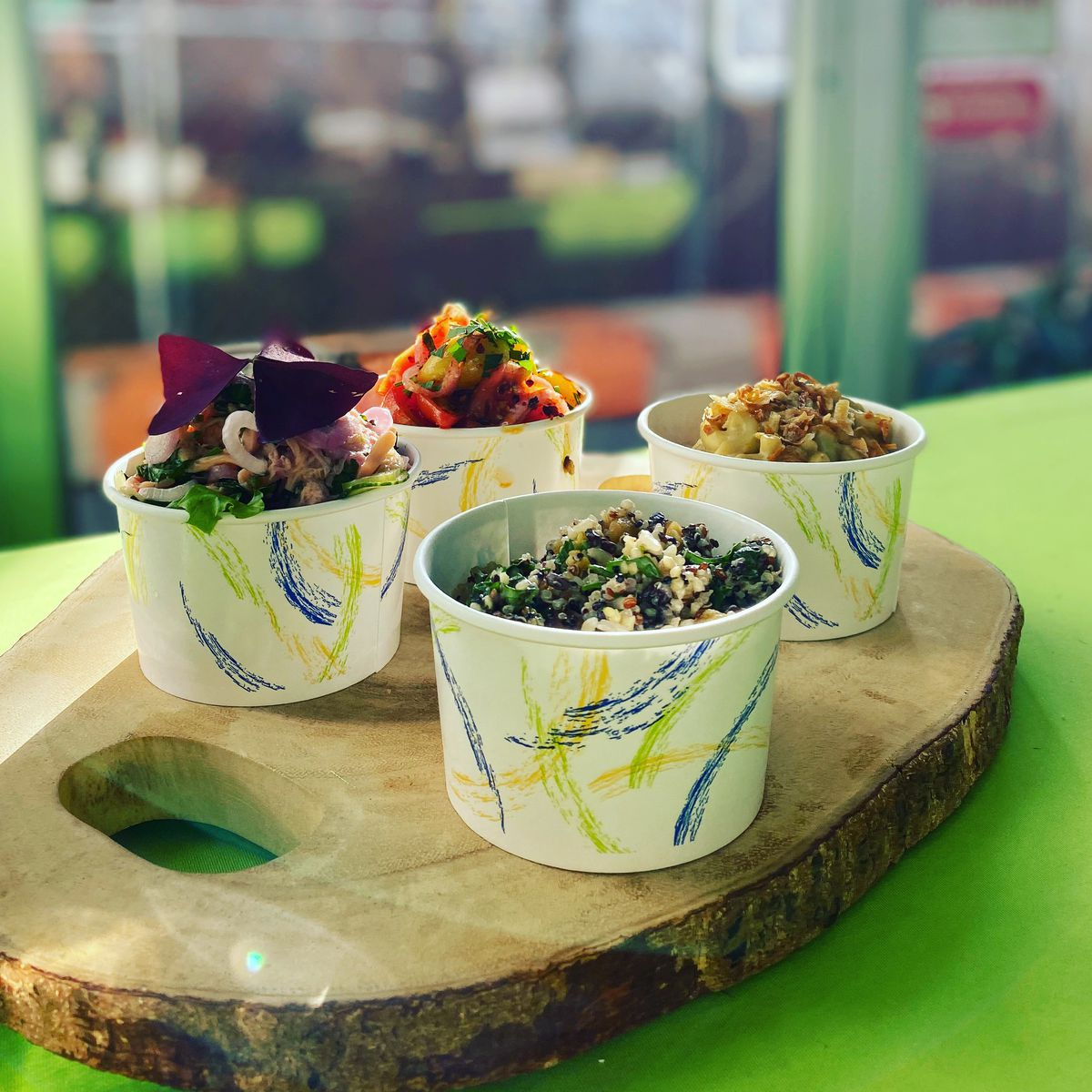 Vegetables and grains overflow from four to-go cups, placed on a wooden cutting board