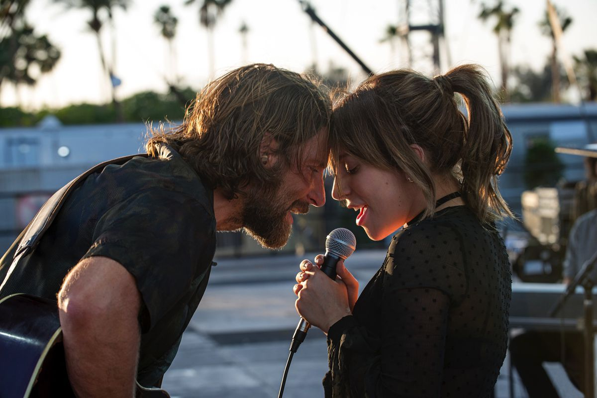 Bradley Cooper and Lady Gaga facing each other and singing into a mic in 'A Star Is Born'