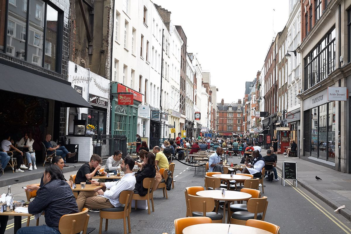 Diners sit at tables on a closed Soho street in summer 2020