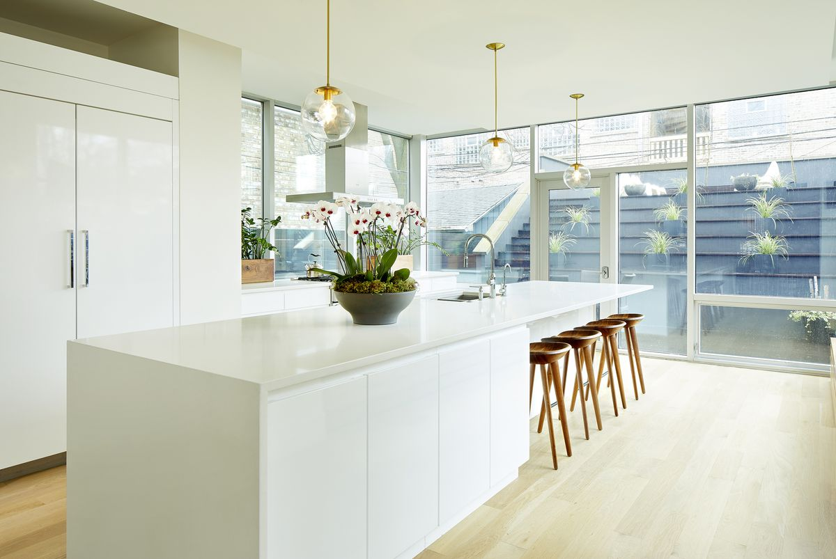 An all-white kitchen is warmed by brass light fixtures and walnut stools.