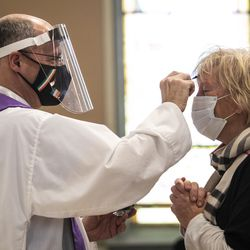 Lori Hiltz, 60, of Streeterville, receives the imposition of ashes from Father Tom Hurley at Old St. Patrick's Catholic Church on the Near West Side on Ash Wednesday. Amid fears of the coronavirus pandemic, Hurley did not touch anyone and gave out ashes on a fresh Q-tip to each congregant, then threw the Q-tip away.