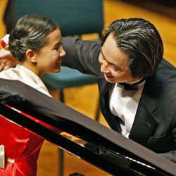Verinas Chen is congratulated by conductor David Cho after performing Franz Liszt's Hungarian Fantasy, S. 123, during the 50th anniversary Salute to Youth concert Tuesday in Salt Lake City.