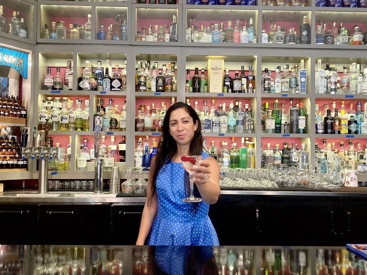 A bartender hands a bright cocktail across a bar, with a large array of backlit bottles of spirits on the backbar