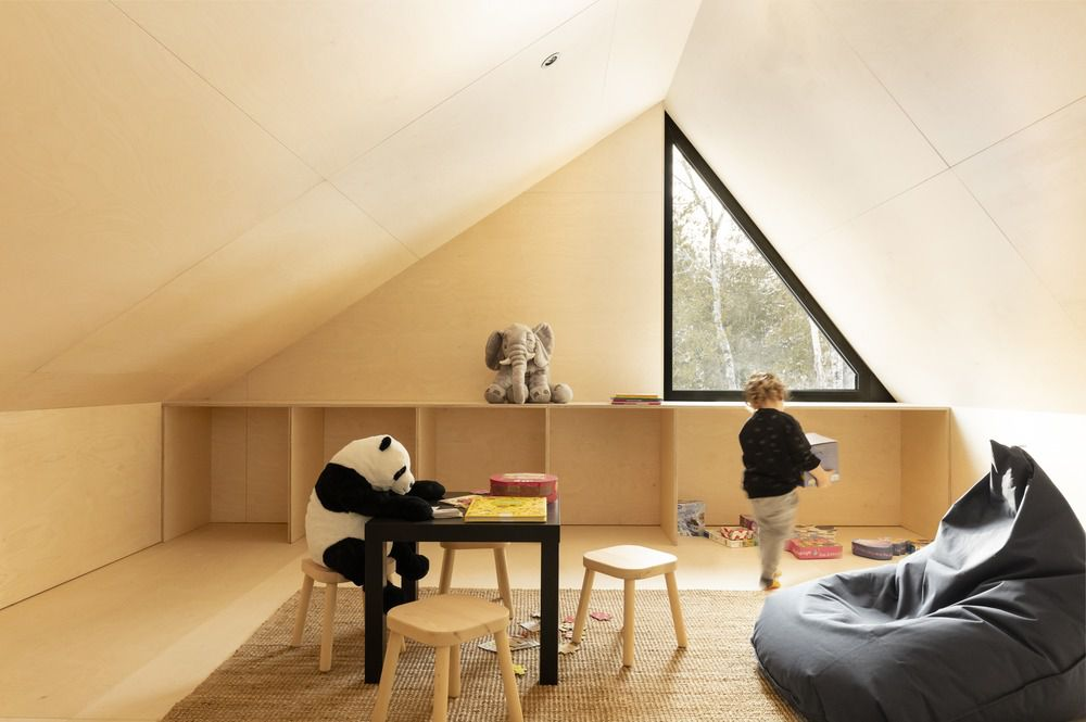 Child in plywood clad playroom with a triangular window.