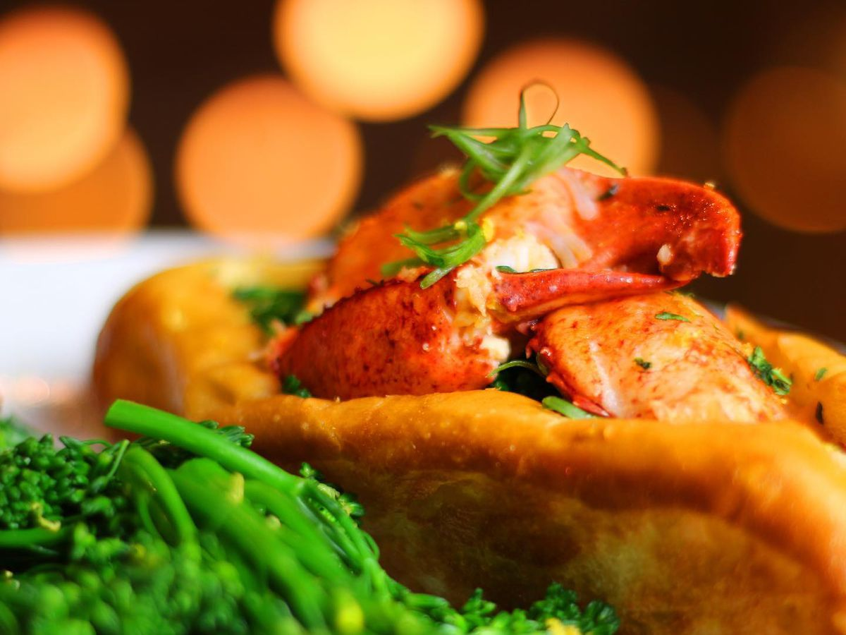 A lobster roll sitting on a white plate with a side of broccolini