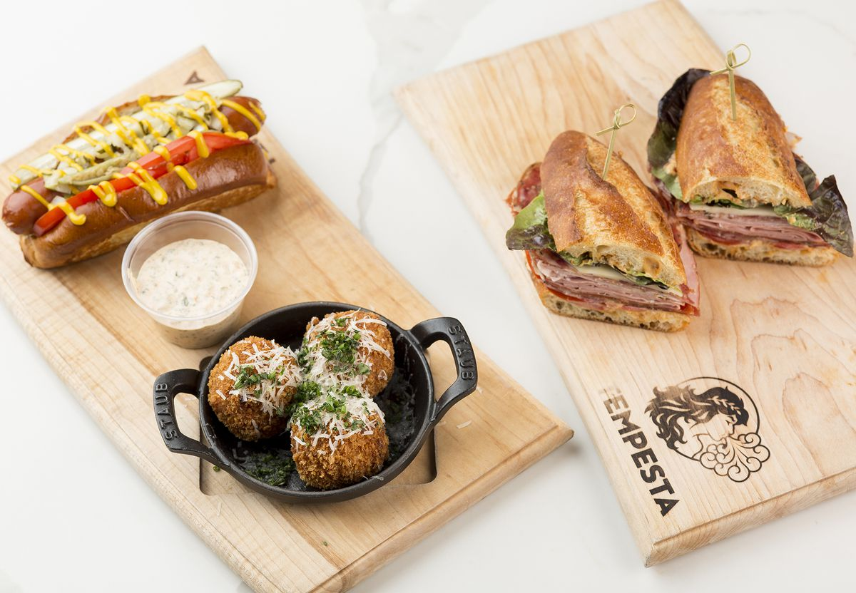 Tempesta Market's Italian sandwich, hot dog, and arancini on wooden boards with logos.