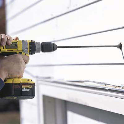 Man Bores Through Garage Wall With Spade Bit For Outdoor Garage Light Installation