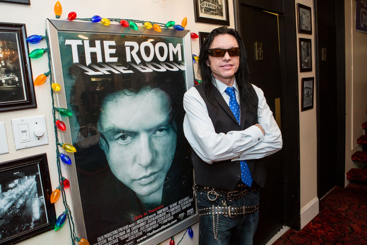 A man in a black vest, blue ties, and sunglasses poses in front of a movie poster in a cinema hallway.