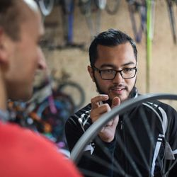 Two men work on a bicycle at the Provo Bicycle Collective.