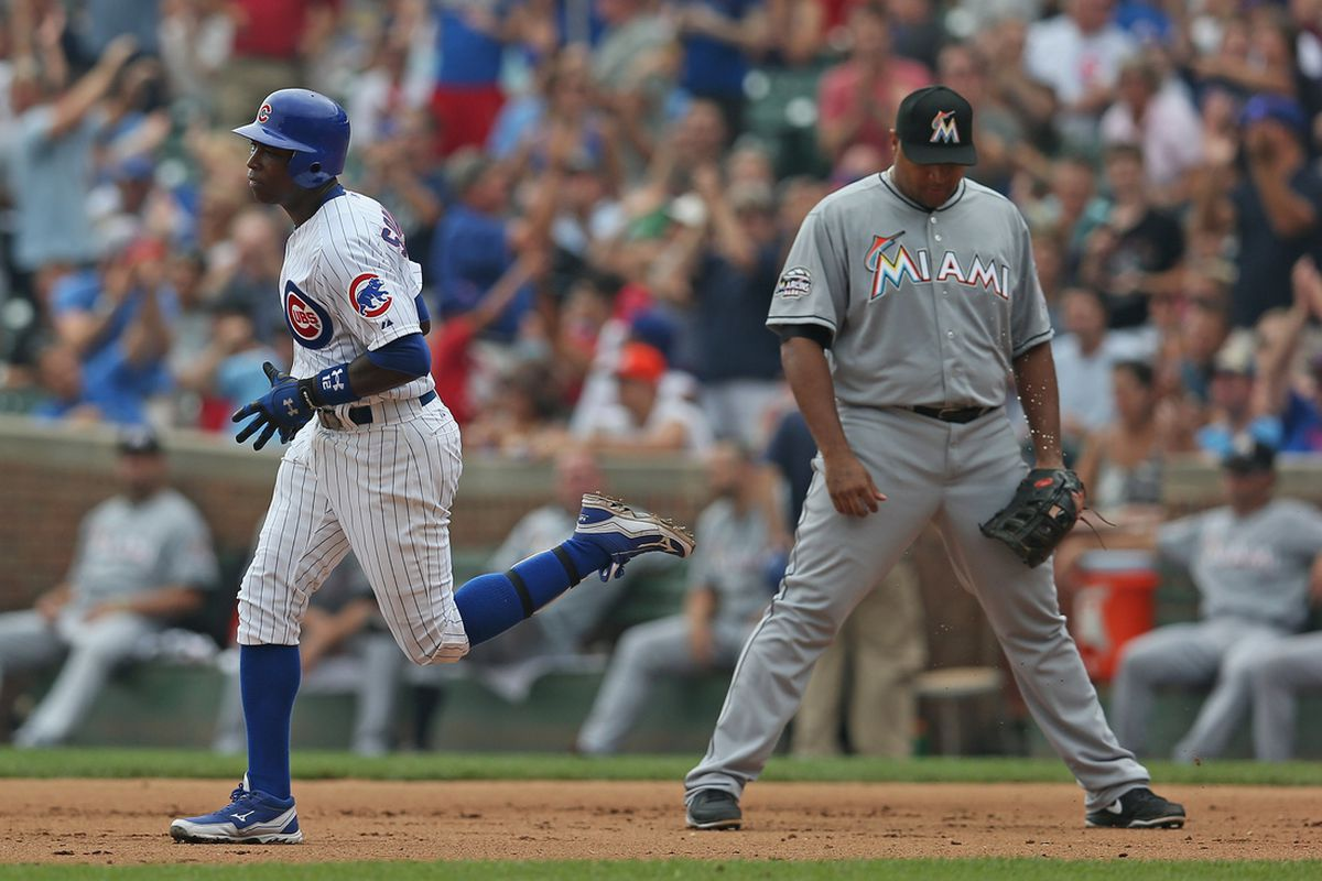 Alfonso Soriano of the Chicago Cubs runs the bases past Carlos Lee of the Miami Marlins after hitting a solo home run at Wrigley Field n Chicago, Illinois. (Photo by Jonathan Daniel/Getty Images)