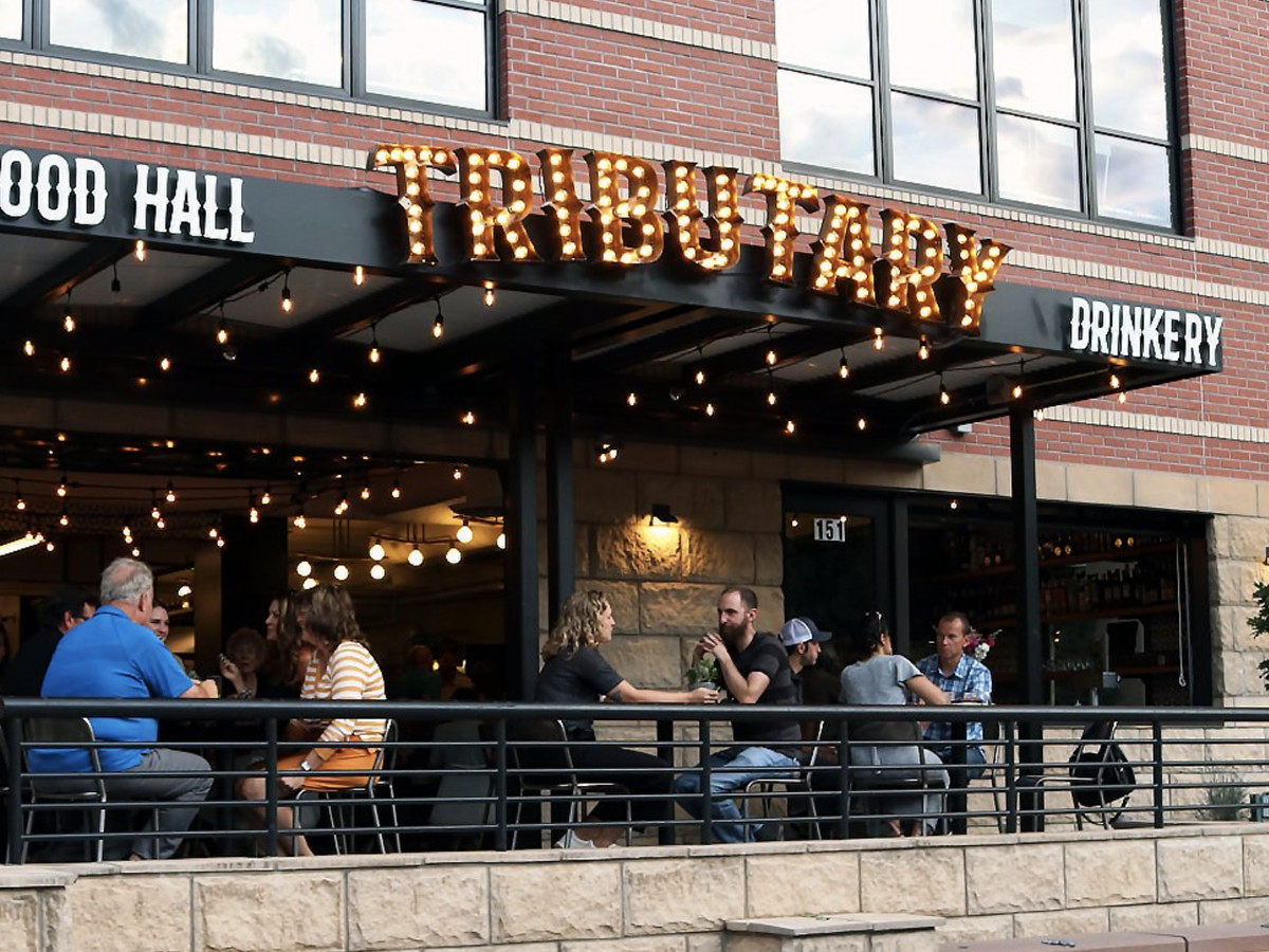 A photo of several people eating and drinking on the patio at Tributary Food Hall in Golden