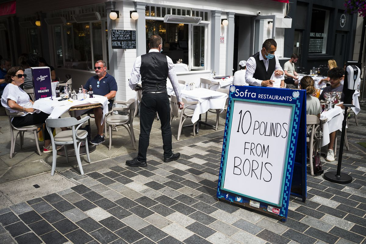 "A sandwich board outside a restaurant where there are outdoor tables and diners, reads, ""10 pounds from Boris."""
