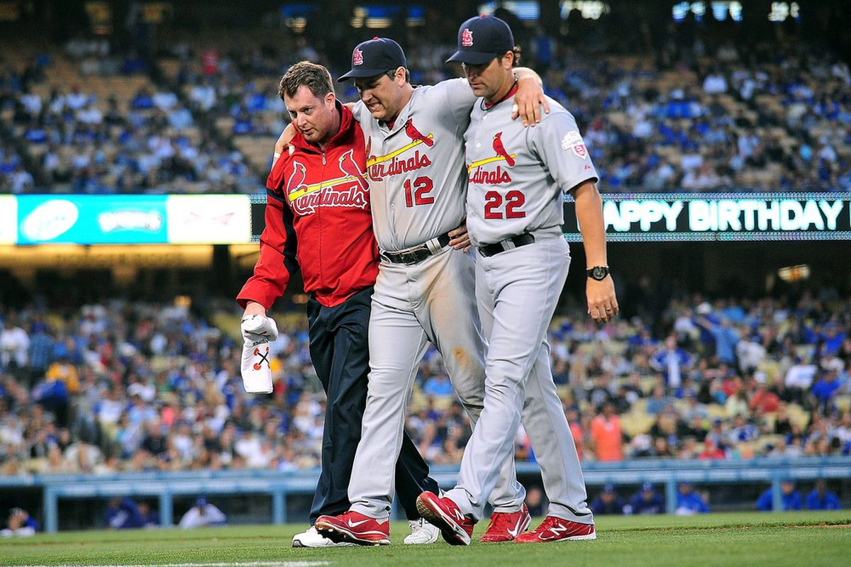 St. Louis Cardinals first baseman Lance Berkman is helped off the field after suffering a knee injury in the second inning against the Los Angeles Dodgers at Dodger Stadium.  Mandatory Credit: Gary A. Vasquez-US PRESSWIRE