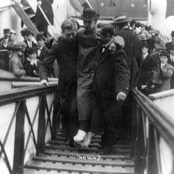 """In this 1912 photo made available by the Library of Congress, Harold Bride, surviving wireless operator of the Titanic, with feet bandaged, is carried up the ramp of a ship. April 15, 2012 is the 100th anniversary of the sinking of the Titanic, just five days after it left Southampton on its maiden voyage to New York. It was a news story that would change the news. From the moment that a brief Associated Press dispatch relayed the wireless distress call _ """"Titanic ... reported having struck an iceberg. The steamer said that immediate assistance was required"""" _ reporters and editors scrambled. In ways that seem familiar today, they adapted a dawning newsgathering technology and organized saturation coverage and managed to cover what one authority calls """"the first really, truly international news event where anyone anywhere in the world could pick up a newspaper and read about it."""" (AP Photo/Library of Congress)"""