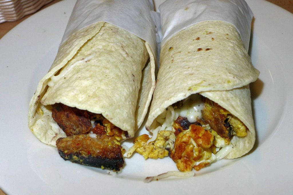 A pair of tacos wrapped in tissue on a white plate.