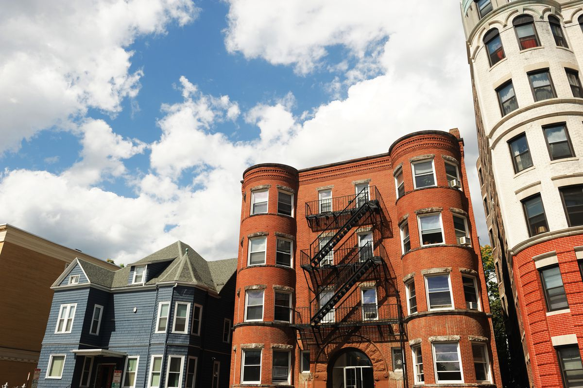 The exteriors of three apartment buildings, each shorter than the last, with a lot of blue sky visible behind.