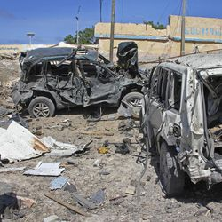 A Somali soldier walks past destroyed vehicles at the scene of a car bomb attack in Mogadishu, Somalia Tuesday, June 20, 2017. A number of people are dead after a suicide car bomber in a vehicle posing as a milk delivery van detonated at a district headquarters in Somalia's capital, police said Tuesday.