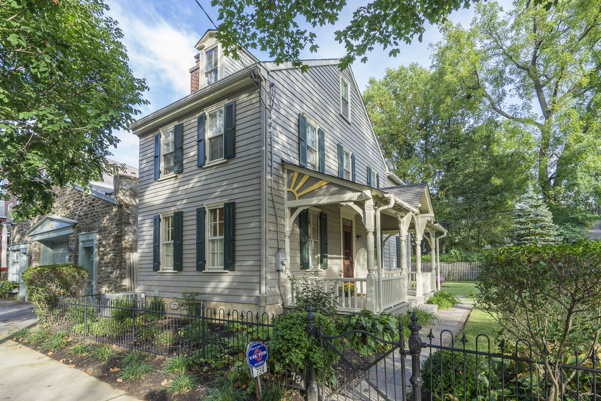 A farmhouse in Philly's Mt. Airy neighborhood with a side porch, green window shutters, and a dormer window.