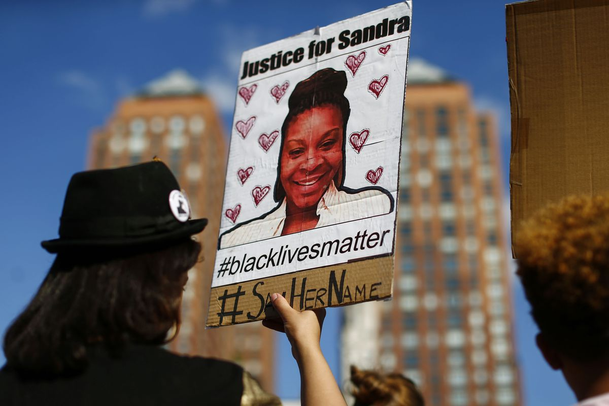 A protester carries a poster honoring Sandra Bland during a memorial rally in 2015.