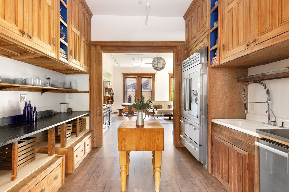 A kitchen with counters on both sides, stainless steel appliances, and a wooden table in the middle.
