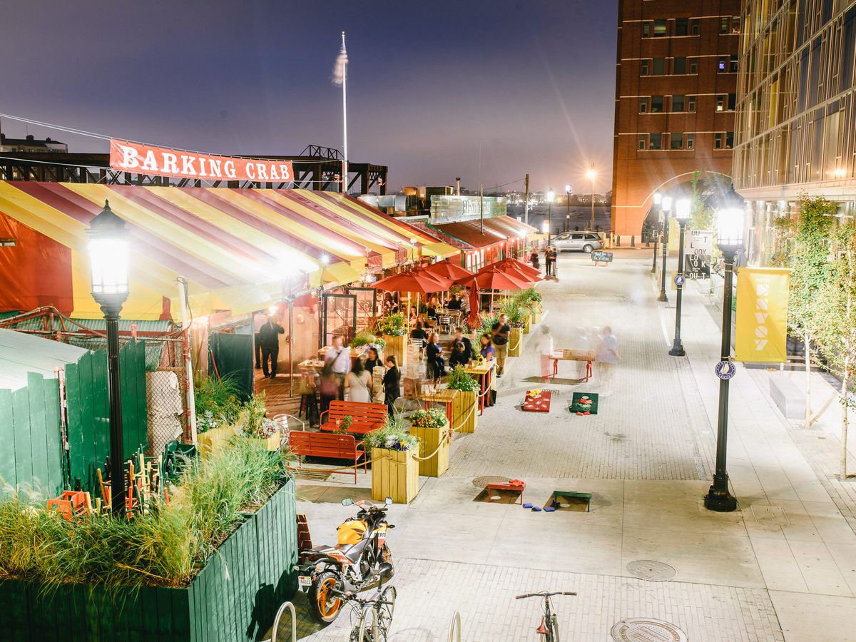 Outside view of the Barking Crab at night, featuring its distinctive red and yellow striped tent