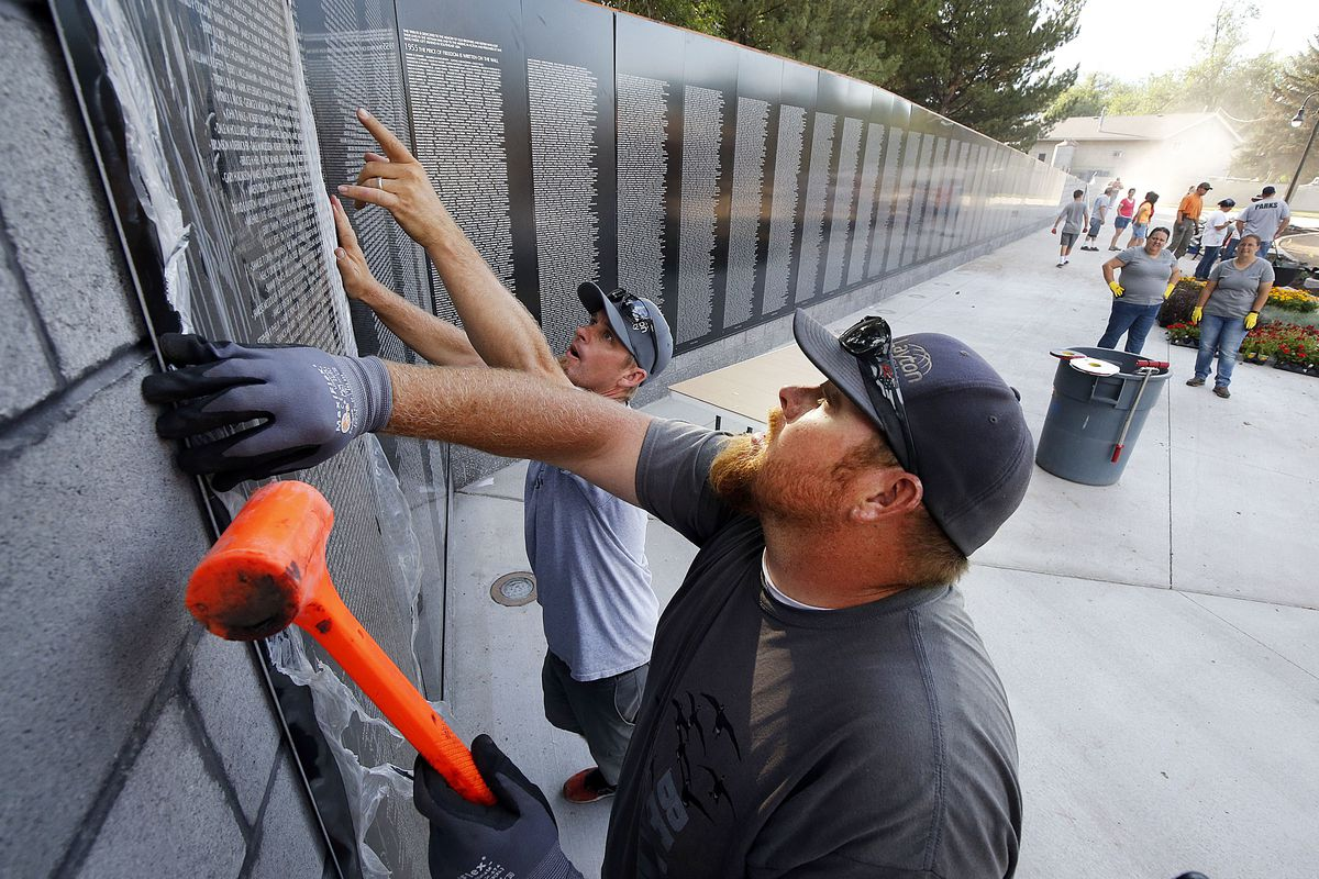 Casey Schroader, front, and Ryan Pickup place a name panel on the Vietnam Memorial Wall in Layton on Tuesday, July 10, 2018.