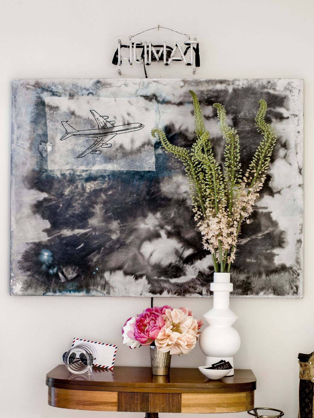 """In the entry, an abstract blue artwork hangs over a console table and below a neon sign that says """"heimat."""""""