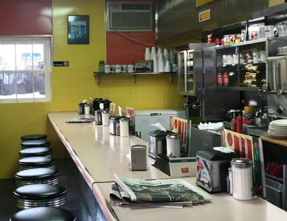 A slim diner counter with a yellow wall in the background shows the majority of the Ideal Diner's seats available inside.