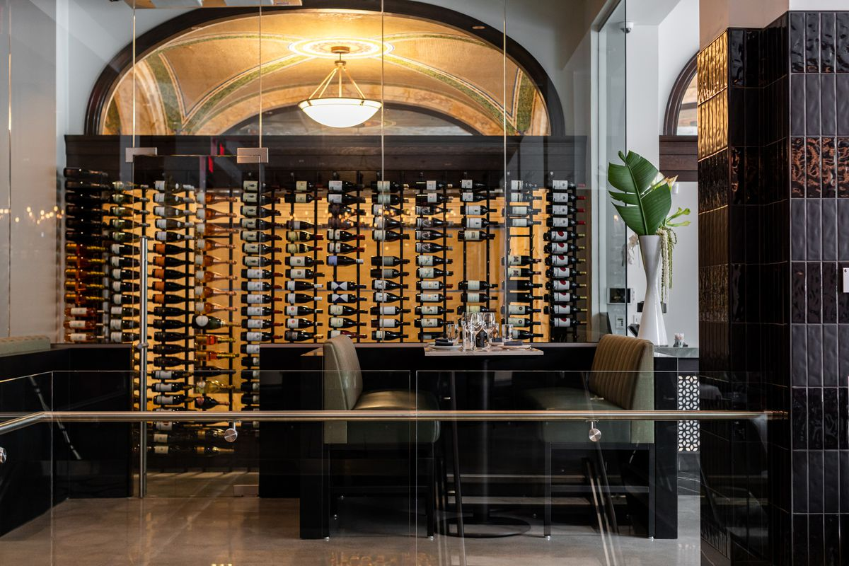 Wine bottles are arranged sideways in a glass case along a wall at Leila.