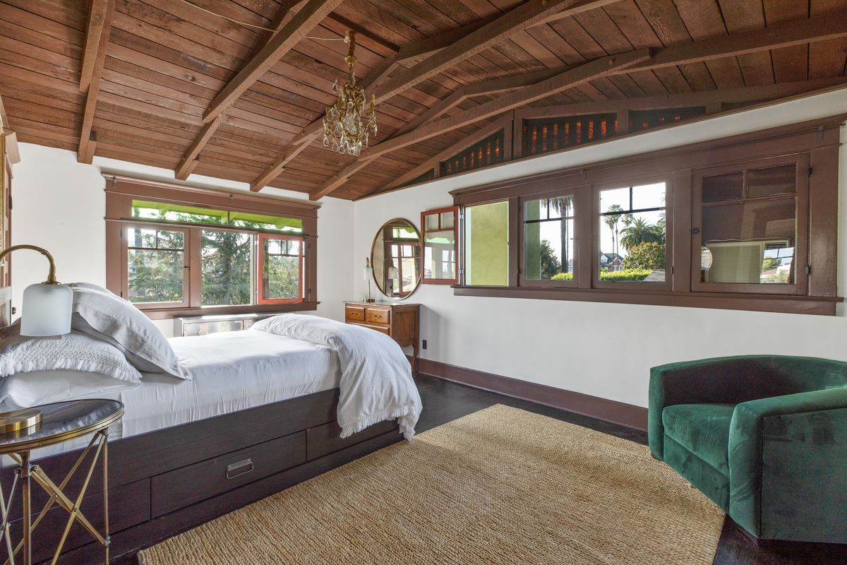 A bedroom with vaulted beam ceilings.