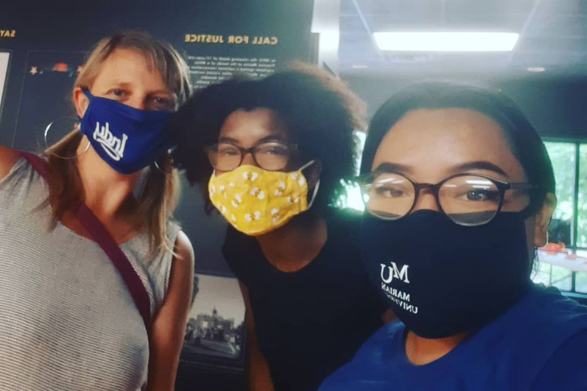 Two young women of color pose with an older white woman at a camp for social justice. They are all wearing protective masks and the two younger women are wearing glasses.