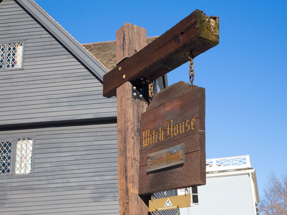 """An old house with a sign outside that says """"Witch House""""."""
