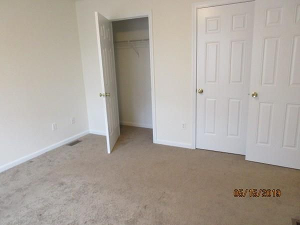 An empty room with carpeting and an opened door into an empty closet.