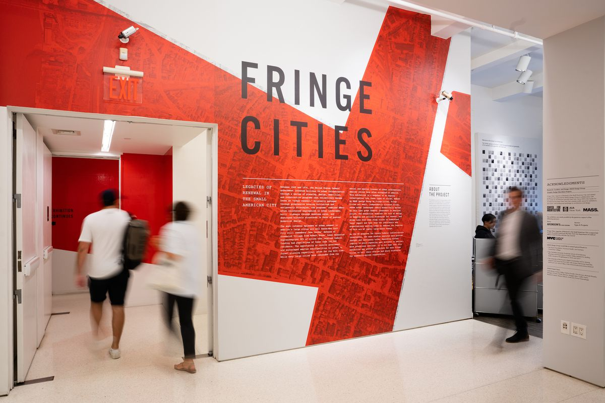 The exhibition title wall showing an enlarged aerial satellite view of a city