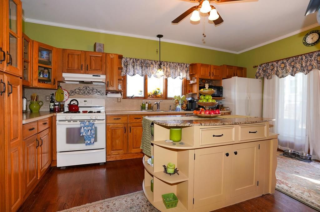 A kitchen with an island in the middle, and the island has built-in shelves.