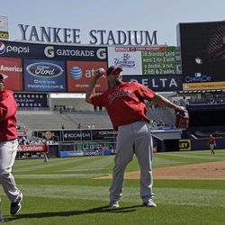 Los Angeles Angels first baseman Albert Pujols, center, throws on the field before the Yankees home opener baseball game against the Los Angeles Angels at Yankee Stadium in New York, Friday, April 13, 2012.